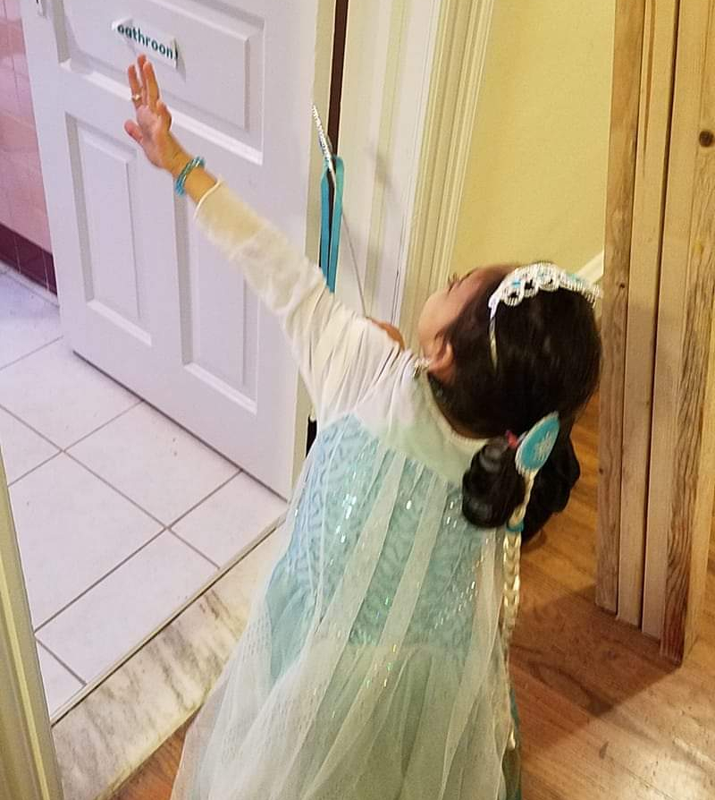 "A young girl in an Elsa costume holds up her hands to ""freeze"" an unseen person."