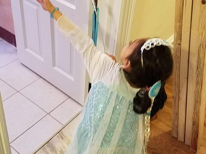 """A young girl in an Elsa costume holds up her hands to """"freeze"""" an unseen person."""